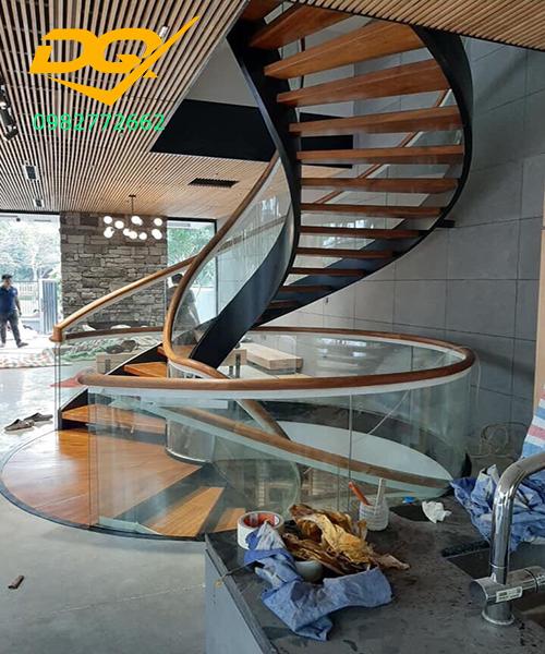 Cầu thang xoắn ốc vách kính tay vịn gỗ